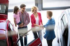 Concessionnaire automobile offrant une voiture à la famille Image stock