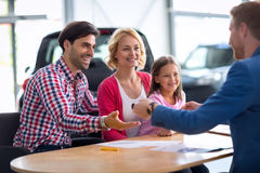 Concessionnaire automobile vendant la nouvelle automobile à la jeune famille avec l'enfant Photographie stock libre de droits