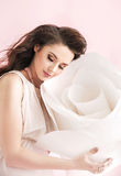 Concetpual image of brunette woman cuddling a giant rose royalty free stock photo