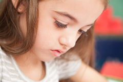 Concetrated girl drawing in her desk royalty free stock photo