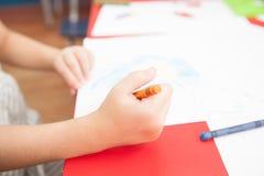Concetrated-Mädchenzeichnung in ihrem Schreibtisch Lizenzfreie Stockfotografie