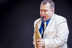 Concetti di musica Giocatore di sassofono maschio caucasico maturo espressivo fotografia stock