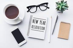 Concetti di risoluzione del nuovo anno con testo sul taccuino e sulla tavola dell'ufficio degli accessori fotografia stock libera da diritti