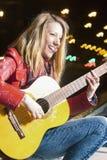 Concetti di vita di via della gioventù Ritratto della ragazza bionda caucasica sorridente che gioca la chitarra fuori sulla via Immagini Stock Libere da Diritti