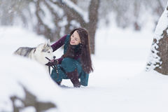 Concetti ed idee degli animali domestici Donna castana caucasica felice e sorridente che gioca con Husky Dog Fotografia Stock Libera da Diritti