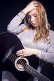 Concetti musicali ed idee Ritratto di posa femminile bionda caucasica con la chitarra Immagine Stock