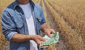 Concetto agricolo, agricoltore, soldi e campo Immagine Stock Libera da Diritti