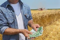 Concetto agricolo, agricoltore, soldi e raccolto Fotografie Stock Libere da Diritti