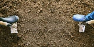 Concetto agricolo con uno spazio della copia Piedi maschii e femminili in scarpe di gomma che scavano terra con le pale sui bordi Immagine Stock