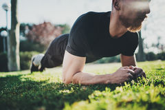Concetto all'aperto di stile di vita di allenamento Giovane uomo barbuto che fa gli esercizi addominali prima della formazione At Immagine Stock