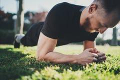 Concetto all'aperto di stile di vita di allenamento Giovane uomo muscolare dell'atleta che fa gli esercizi addominali prima della Fotografia Stock Libera da Diritti