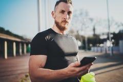 Concetto all'aperto di stile di vita di allenamento Il giovane che allunga il suo braccio muscles prima della formazione Usando m Immagine Stock