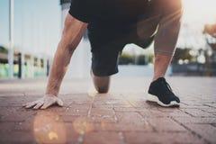 Concetto all'aperto di stile di vita di allenamento Il giovane che fa l'allungamento esercita i muscoli prima della formazione Es Fotografie Stock Libere da Diritti