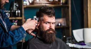 Concetto alla moda di taglio di capelli Mani del barbiere con la fine del tagliatore su Cliente con la barba sul fondo del salone fotografia stock libera da diritti