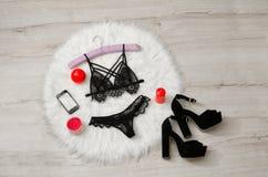 Concetto alla moda, un insieme della biancheria intima di pizzo, telefono, scarpe e candele rosse sulla pelliccia bianca vista su Fotografia Stock