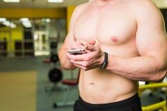 Concetto astuto di forma fisica di allenamento Primo piano di giovane atleta muscolare che controlla programma di formazione sull Fotografie Stock Libere da Diritti