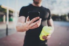 Concetto astuto di sessione di allenamento Giovane atleta muscolare che controlla il programm di addestramento sull'applicazione  Fotografia Stock
