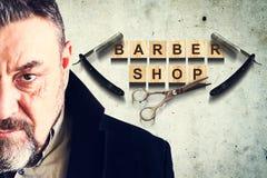 Concetto Barber Shop Uomo barbuto sui precedenti di un muro di cemento Negozio di barbiere dell'iscrizione Bellezza e modo immagini stock