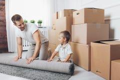 Concetto commovente, padre e figlio muoventesi verso una nuova casa fotografia stock libera da diritti