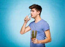Concetto con un uomo che tiene un cactus e glace di acqua Fotografie Stock