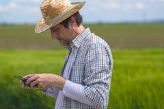 Concetto d'agricoltura astuto, agricoltore che utilizza fuco nel campo Immagini Stock