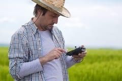 Concetto d'agricoltura astuto, agricoltore che utilizza fuco nel campo Immagini Stock Libere da Diritti