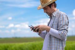 Concetto d'agricoltura astuto, agricoltore che utilizza fuco nel campo Immagine Stock