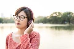 Concetto d'ascolto di musica della giovane donna asiatica Immagine Stock