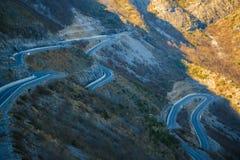 Concetto d'esplorazione di viaggio - strada curvy nelle alte alpi albanesi Fotografia Stock