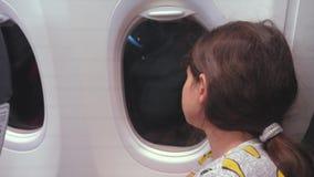 Concetto degli aerei di aviazione il giovane adolescente che esamina piano vola alla finestra di notte durante il volo Giovane pa stock footage