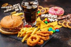 Concetto degli alimenti industriali Fondo non sano dell'alimento Alimenti a rapida preparazione e zucchero Hamburger, dolci, chip immagine stock libera da diritti