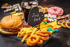 Concetto degli alimenti industriali Fondo non sano dell'alimento Alimenti a rapida preparazione e zucchero Hamburger, dolci, chip immagini stock libere da diritti