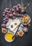 Concetto degli aperitivi per vino, il formaggio del camembert, l'uva scura, le noci ed i fichi con miele, su un fondo rustico di  immagini stock