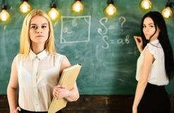 Concetto degli apprendisti e degli studenti La ragazza sembra sicura mentre scrittura di signora sul fondo della lavagna, defocus Fotografie Stock Libere da Diritti
