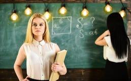 Concetto degli apprendisti e degli studenti La ragazza sembra sicura mentre scrittura di signora sul fondo della lavagna, defocus Fotografia Stock