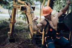 Concetto degli impiegati Bicipite della flessione degli impiegati e muscolo del tricipite Impiegato forte alla cabina dell'escava immagini stock libere da diritti