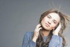 Concetto dei capelli: Castana sensuale con della mosca i capelli via Fotografia Stock