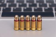 Concetto dei pericoli di Internet Chiuda su delle pallottole e della tastiera del computer portatile Fotografia Stock