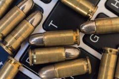 Concetto dei pericoli di Internet Chiuda su delle pallottole e della tastiera del computer portatile Immagine Stock Libera da Diritti