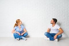 Concetto dei problemi di alloggio di ipoteca coppie alla parete in bianco Fotografia Stock