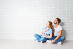 Concetto dei problemi di alloggio di ipoteca coppie alla parete in bianco Immagine Stock Libera da Diritti
