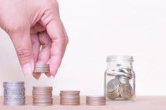 Concetto dei soldi di risparmio Chiuda sulle monete della pila della maniglia a arrang Immagini Stock