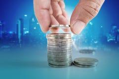 Concetto dei soldi di risparmio mano che mette moneta alle pile di monete Immagine Stock