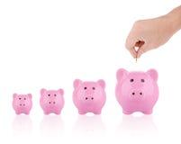 Concetto dei soldi di risparmio - mettere moneta nel porcellino salvadanaio Fotografia Stock Libera da Diritti
