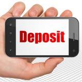 Concetto dei soldi: Mano che tiene Smartphone con il deposito su esposizione Immagini Stock