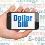 Concetto dei soldi: Mano che tiene Smartphone con la banconota in dollari su esposizione Immagine Stock