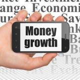 Concetto dei soldi: Passi la tenuta dello Smartphone con la crescita di soldi su esposizione Immagini Stock Libere da Diritti