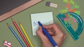 Concetto del banco BIOLOGIA di scrittura della mano della donna sul blocco note archivi video