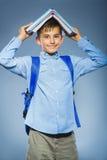Concetto del banco riuscito ragazzo felice del ritratto con il libro della tenuta dello zaino sulla sua testa Fotografia Stock
