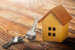 Concetto del bene immobile con la casa di legno del piccolo giocattolo e chiave su fondo di legno Idea per il concetto del bene i immagine stock libera da diritti